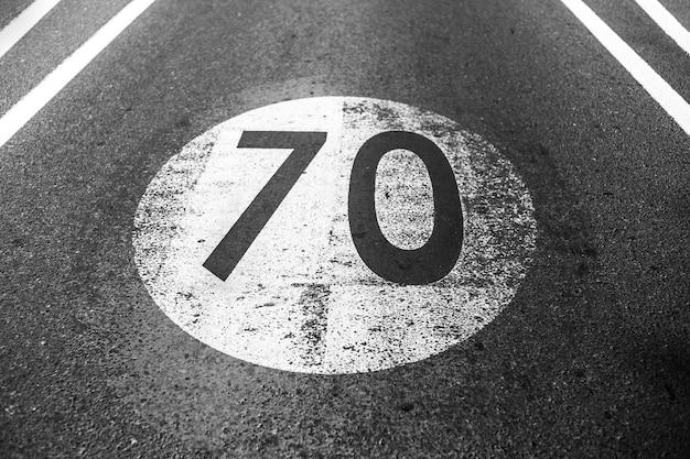 Foto in bianco e nero del vecchio segnale limite di velocità squallido con 70 km all'ora, dipinto su strada asfaltata.