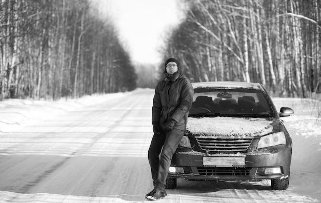 Foto in bianco e nero della strada rurale invernale nella foresta in una giornata di sole e uomo con auto