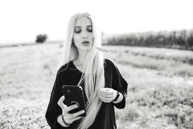 Foto in bianco e nero di giovane ragazza bionda che tiene uno smartphone, nel campo.