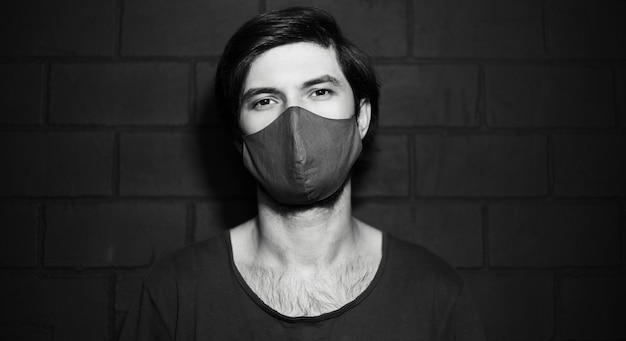 Foto in bianco e nero di un giovane che indossa una maschera medica contro un muro di mattoni. Foto Premium