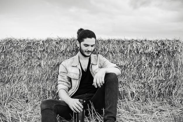 Foto in bianco e nero di un giovane con i capelli lunghi, seduto nel campo di grano.