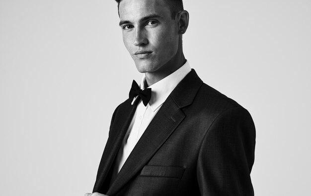Fotografia in bianco e nero di un uomo con una giacca, una camicia e un farfallino al collo. foto di alta qualità