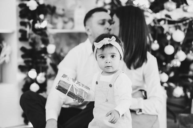 Foto in bianco e nero di papà, mamma con la loro piccola figlia nell'atmosfera di capodanno