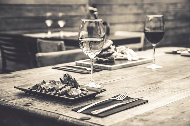 Immagine in bianco e nero dell'atmosfera tradizionale del ristorante con tataki di tonno e hamburger con patatine sullo sfondo su tavola in legno rustico e bicchiere di vino bianco
