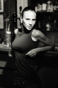 Immagine in bianco e nero di yang e bella donna in piedi accanto al bancone del bar