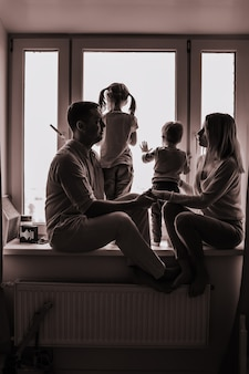 Ritratto in bianco e nero della famiglia caucasica che guarda fuori dalla finestra