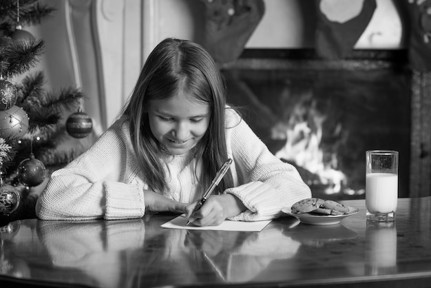 Ritratto in bianco e nero di una ragazza carina che scrive una lettera a babbo natale