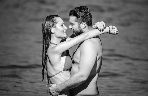Ritratto in bianco e nero delle coppie europee che abbracciano nel mare.