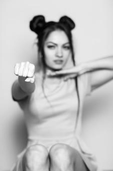 Il ritratto in bianco e nero della giovane donna bruna malvagia con i pugni si concentra sulla mano