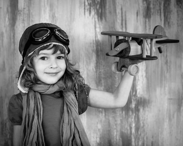 Ritratto in bianco e nero di un bambino felice che gioca con un aeroplano di legno giocattolo al chiuso
