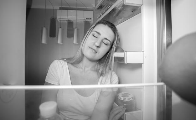Ritratto in bianco e nero di una donna assonnata che si appoggia allo scaffale del frigorifero e cerca di dormire