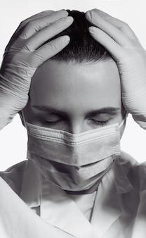 Ritratto in bianco e nero di medico femminile stanco che mette le mani sulla testa