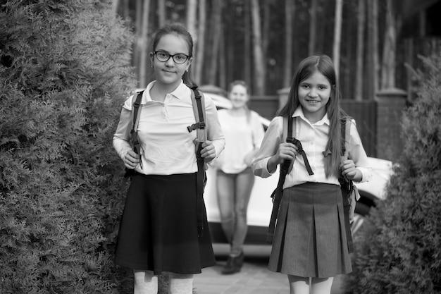 Ritratto in bianco e nero di due ragazze allegre che vanno a scuola al mattino