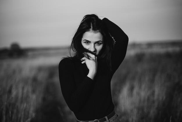 Ritratto in bianco e nero di una ragazza che propone ragazza caucasica del brunette in un maglione