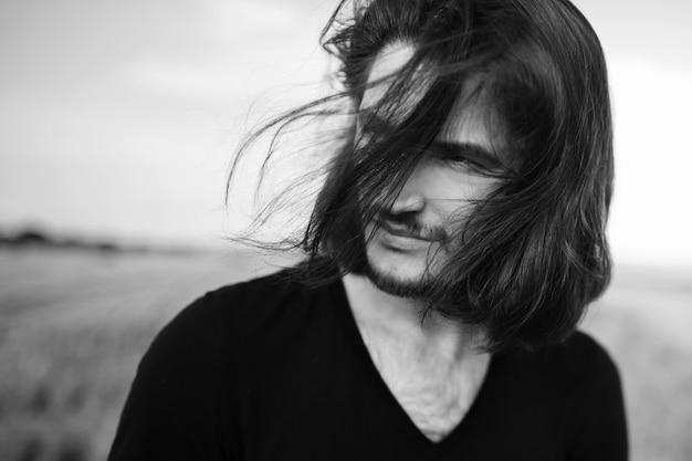 Ritratto in bianco e nero di giovane uomo dai capelli lunghi, concetto all'aperto.
