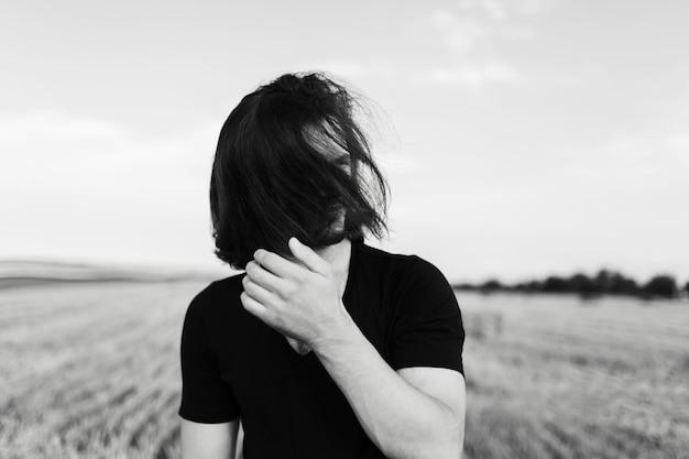 Ritratto in bianco e nero di giovane con i capelli lunghi sul viso.