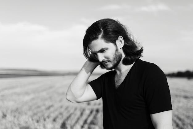 Ritratto in bianco e nero del giovane con capelli lunghi nel campo.