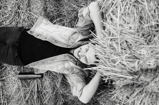 Ritratto in bianco e nero di giovane uomo rilassato sdraiato sul campo di grano.