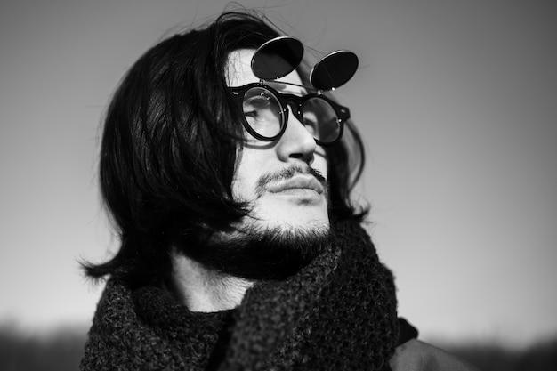 Ritratto in bianco e nero di giovane uomo alla moda con capelli lunghi e sfumature.