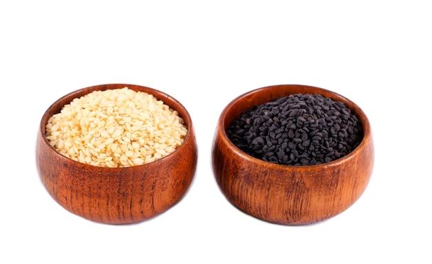Semi di sesamo in bianco e nero in ciotole di legno su sfondo bianco