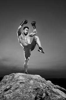 Colpo in bianco e nero di un combattente maschio che esegue kickboxing allenamento all'aperto e allenarsi esercitando combattimento marziale rafforzare il concetto di corpo abs potente energico attivo atletica muscoli torso.
