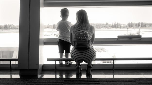 Sagoma in bianco e nero di giovane madre con figlio piccolo in piedi alla finestra nel terminal dell'aeroporto.