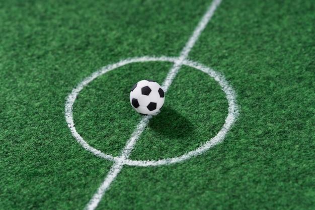 Pallone da calcio in bianco e nero al centro della decorazione del campo da calcio mini football