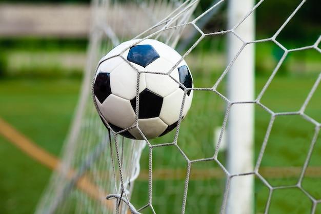 Pallone da calcio in bianco e nero nel cancello. concetto di vittoria nella partita