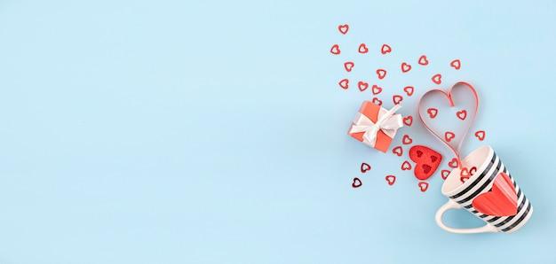 Tazza da caffè a righe bianche e nere con cuore rosso, scatola regalo rossa e decorazioni a cuore