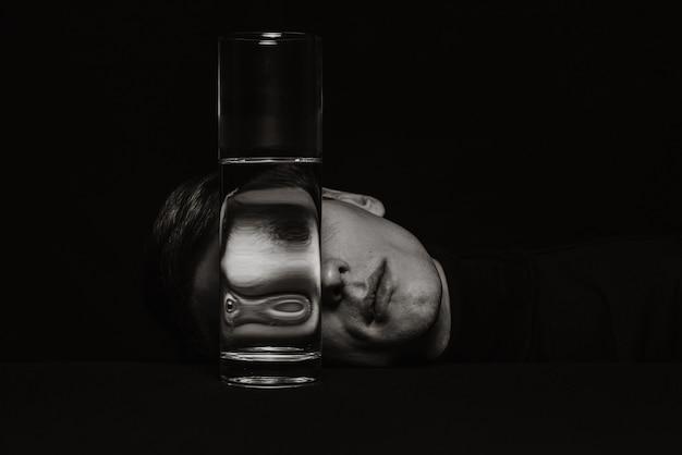 Ritratto surreale in bianco e nero di un uomo attraverso il bicchiere di una lattina d'acqua