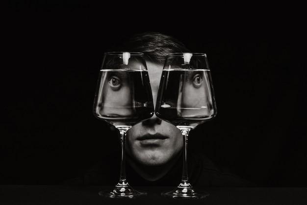 Ritratto surreale in bianco e nero di uno strano uomo che guarda attraverso due bicchieri d'acqua