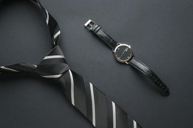 Cravatta bianca e nera e orologio da polso classico su sfondo nero. accessori moda uomo. disposizione piatta.