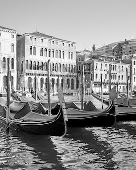Vista in bianco e nero del canal grande a venezia con gondole ormeggiate, italy
