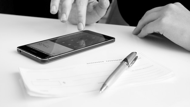 Vista in bianco e nero della donna che fa calcoli finanziari sullo smartphone prima di firmare l'assegno bancario.