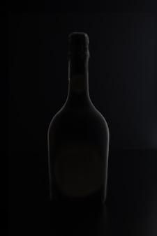 Modello di bottiglia di vino nero senza etichetta su sfondo nero