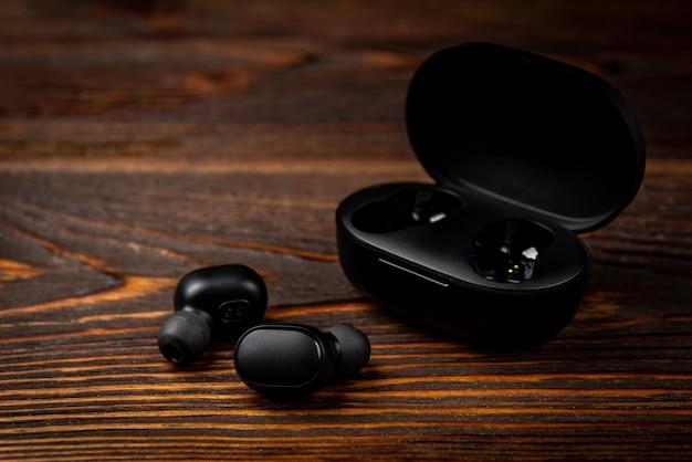 Cuffie senza fili nere su fondo di legno scuro.