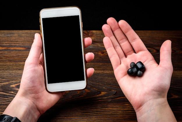 Cuffie senza fili nere e telefono cellulare su fondo di legno scuro.