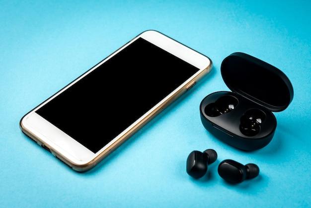Cuffie wireless nere e telefono cellulare bianco su sfondo blu.