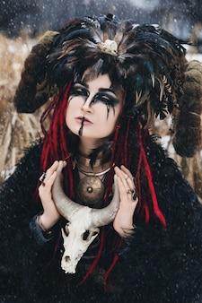 Strega nera in una corona con corna e piume in un mantello di pelliccia nera in una tempesta di neve