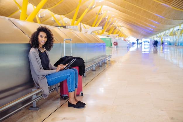 Donna di colore all'aeroporto utilizzando tablet e ascolto musica con le cuffie