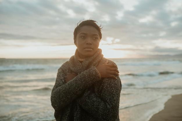 Donna di colore sulla spiaggia al tramonto