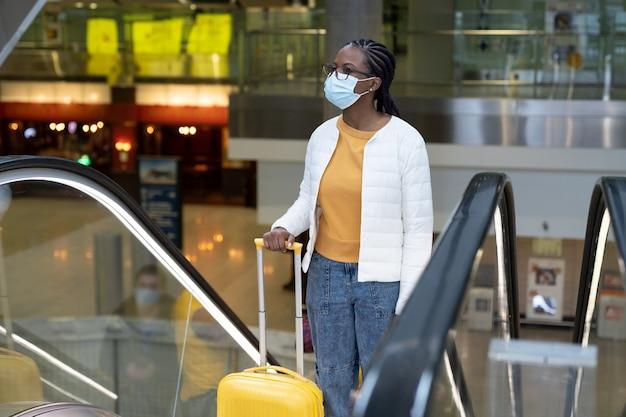 Donna nera in maschera facciale con la valigia sulla scala mobile in aeroporto o stazione ferroviaria viaggiare sotto covid
