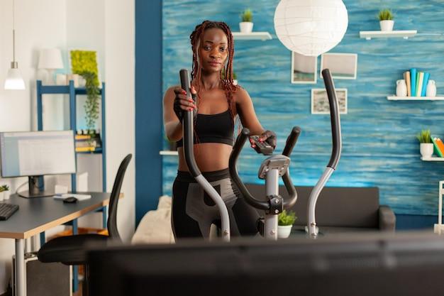 Istruttore di fitness donna nera che si allena nel soggiorno di casa, facendo allenamento cardio usando la macchina da corsa ellittica e guardando lo spettacolo televisivo tenendo il telecomando