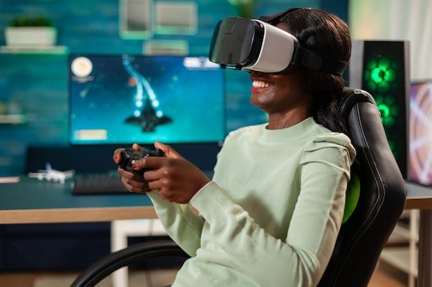Donna di colore che si diverte a giocare ai videogiochi con auricolare vr con controller. campionato di videogiochi sparatutto spaziale virtuale nel cyberspazio, giocatore di esport che si esibisce su pc durante il torneo di gioco.