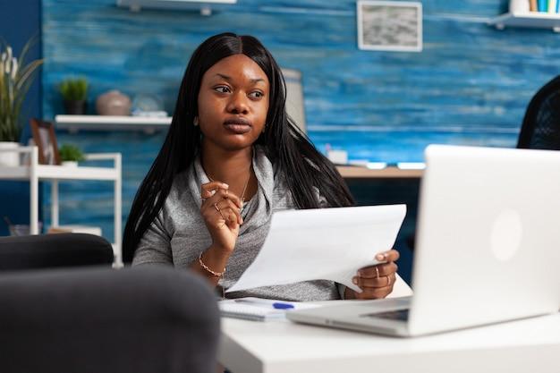 Donna di colore che esamina la strategia di contabilità sul monitor utilizzando il computer portatile