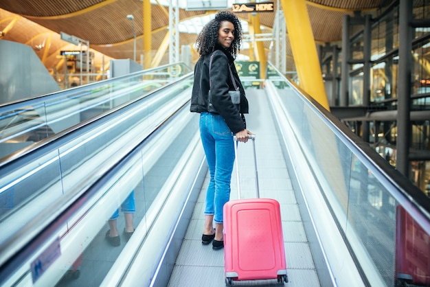 Donna di colore nella passerella in movimento in aeroporto con una valigia rosa.