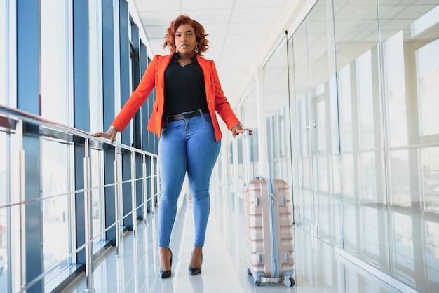 Donna nera nel marciapiede mobile in aeroporto con una valigia rosa