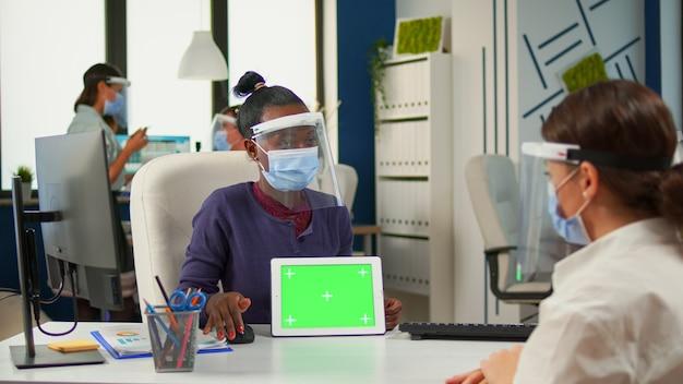 Donna di colore che mostra al manager con tablet maschera facciale con schermo verde, che punta sul display mockup nel nuovo normale ufficio aziendale rispettando la distanza sociale