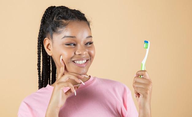 La donna di colore sorride con denti bianchi e perfetti mentre tiene in mano uno spazzolino da denti