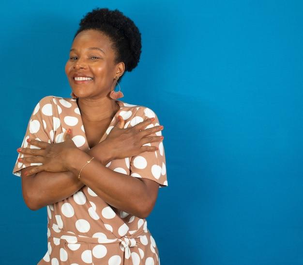 Donna nera che sorride e che si abbraccia con una parete blu
